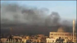 This image made from amateur video and released Wednesday by Shaam News Network purports to show black smoke from shelling billowing into the sky air in Aleppo, Syria.