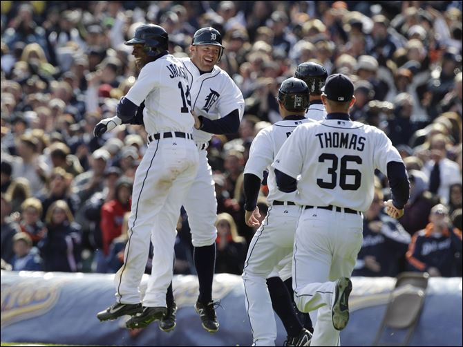 The Detroit Tigers rush to congratulate Austin Jackson, left, after his bases-loaded game-winning single in the ninth inning of a baseball game against the Boston Red Sox in Detroit. Detroit won 3-2.