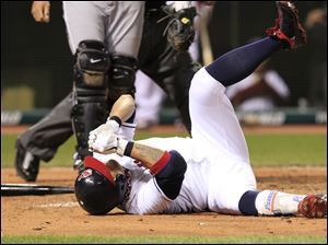Cleveland Indians' Shin-Soo Choo rolls on the ground after getting hit by a pitch in the left hand in the sixth inning in a baseball game against the Chicago White Sox in Cleveland.