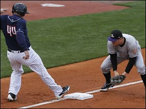 Mud Hens designated hitter Brad Eldred stays on third base after the hitter is outed at first.