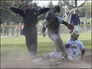 Spartans catcher Jake Cannon dropped the ball, allowing a run by St. Johns'  Jesse Adams.