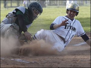 Spartans catcher Jake Cannon tries to tag St. Johns'  Jesse Adams at the plate.