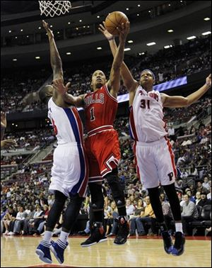 Bulls guard Derrick Rose (1) drives between Pistons defenders Rodney Stuckey, left, and Charlie Villanueva.