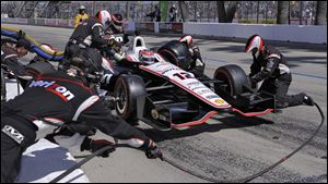 Will Power's crew works to get him back on the track during a pit stop. Power is the points leader after the win.