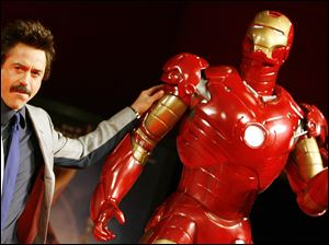 "In this 2008 file photo,  U.S. actor Robert Downey Jr. poses with a life-size ""Iron Man."""