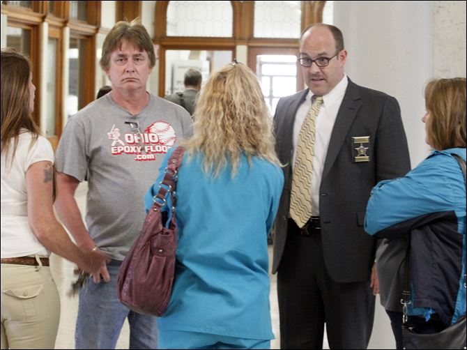 CTY clement16p Lawrence Clement, 57, center, talks with court Deputy Kevin Wiezbinski, front left, after his arraignment  on Monday for one count of abuse of a corpse. Mr. Clement is flanked by his wife, left, and mother-in-law, in white at right, and faces his attorney Ann Baronas.