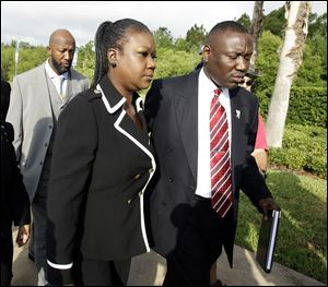 Tracy Martin, back left, and Sybrina Fulton, center, parents of Trayvon Martin, arrive Friday with attorney Benjamin Crump at the Seminole County Criminal Justice Center for a bond hearing for George Zimmerman,  the neighborhood watch volunteer charged with murdering their son.