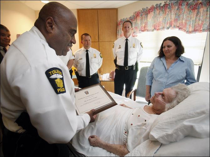 hard work deserves recognition-2 Toledo police Chief Derrick Diggs honors Evelyn Feiger with an award recognizing her volunteer efforts to the city of Toledo. Ms. Feiger is a resident of Lutheran Village at Wolf Creek in Springfield Township. With Chief Diggs are Lts. James Brown and Mark King and Bea Harris, a family friend.