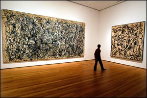 A visitor strolls by canvasses by Abstract Expressionist Jackson Pollock at the Museum of Modern Art in New York.