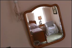 Guest bedroom furnishings are reflected in a mirror at the Winter House.