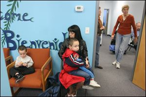 Victoria Bernal and sons Justice, 5, in her lap, and Jace, 2, wait their turn at the Providence Center food pantry in South Toledo. They get by on child support, $328 a month in food stamps, and the occasional odd job, Ms. Bernal said.