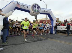 Marathon and half-marathon runners cross the starting line of the Glass City Marathon Sunday.