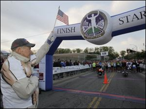 Tom Falvey holds a U.S. flag as the national anthem is played before the start of the marathon.