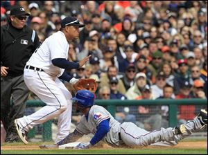 Texas Rangers' Elvis Andrus, right, safely slides into third base as Detroit Tigers third baseman Miguel Cabrera, center, waits for the throw from the outfield during the eighth inning of a baseball game in Detroit Sunday. Andrus scored on a sacrifice hit by teammate Josh Hamilton.