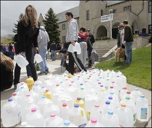 Students Anna Konwinski, of Troy, Mich., and Brian Wellman of Coldwater, Ohio, pick up gallon water jugs for the march around the University of Toledo campus.