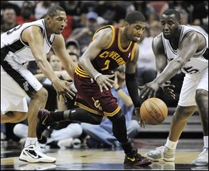 Cleveland's Kyrie Irving, center, fights for a loose ball against the  Spurs' Boris Diaw, left, and DeJuan Blair during the first half.