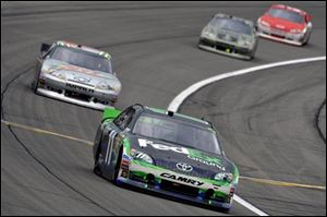 Denny Hamlin (11) leads during the NASCAR Sprint Cup Series auto race at Kansas Speedway.
