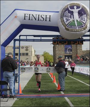 Jessica Odorcic of Madison, Ohio, in the northeast corner of the state, crosses the finish line first in the women's division. Her winning time was 2 hours, 51 minutes, 52 seconds. The Glass City win was her first marathon.