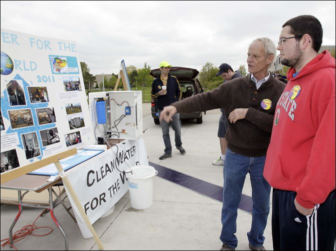 UT rally pushes for global access to clean water Paul Flickinger of Kalamazoo, Mich., left, speaks with UT student Chris Etzinger of Fostoria about the mission of Clean Water for the World and the water-purification system at left, which is destined for Haiti.  Saturday's event coincided with Earth Day weekend.