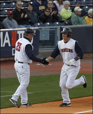 Mud Hens manager Phil Nevin shakes hands with Ryan Strieby as he rounds 3rd base. Strieby hit a home-run in the 1st inning against Columbus at Fifth Third Field.