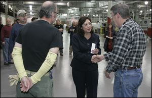 U.S. Labor Secretary Hilda Solis shakes hands with worker Dale Brossia at Willard & Kelsey in February, 2011. Vice President Joe Biden also has visited the plant.