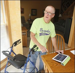 Tim Brooks, 54, who is retired from FirstEnergy Corp., uses a walker to get around and continues to fish and do other activities. His case of ALS is among the roughly 10 percent involving a gene abnormality shared by family members.