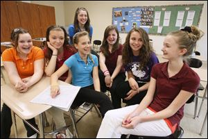 The seventh grade team from Byrnedale Elementary School in Toledo, that won the Blade's annual Student Stock Contest,  talks about how they picked their winning portfolio of stocks.  Team members from left are Emma Hansen, Marissa Hagen, Vanessa Skouroukos (back),  Emily Bettinger (with hand on stock page in Blade), Julie Bratton, Madison Huffman, and Kelsey Tiell. Not present for photo was Marisela Ruiz.