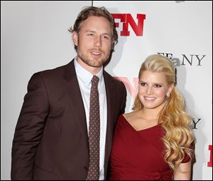 Singer Jessica Simpson, right, poses with her fiance Eric Johnson at the 25th Annual Footwear News Achievement Awards in November. The couple welcomed their baby girl into the world today.