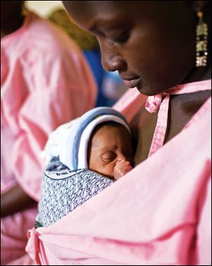 A mother carrys her unnamed twin baby, 11 days old, in the Kangaroo Care center at the Gabrielle Traoré Hospital in Bamako, Mali.