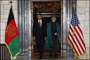President Barack Obama and Afghan President Hamid Karzai arrive before signing a strategic partnership agreement, Tuesday, May 1, 2012, at the presidential palace in Kabul, Afghanistan.