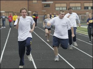 Whitmer High School students Kevin Reau, 15, left, and Derrick Hurst, 18, running first and second in the 100m.   Washington Local Schools (WLS) is holding its first Infinite Opportunity Olympics at Whitmer High School's Memorial Stadium in Toledo, Ohio on May 5, 2012. In the games, WLS students with disabilities compete against each other in track and field events. Members of the Whitmer High School Girls' Track team are paired with the participants to serves as guid