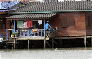 A man fishes in the Chao Phraya River in Bangkok. As the climate changes and the seas rise, cities such as Bangkok and even London and New York could become 'hydro-cities.' 'We will have to live with a more watery environment. There is no choice,' says Danai Thaitakoo, a Thai landscape architect.