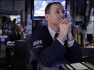 Specialists Chris Gildea, left, and Stephen Naughton work on the floor of the New York Stock Exchange today. Political uncertainty in debt-hobbled Europe spread to financial markets Tuesday and pushed stocks sharply lower in Europe and the United States.