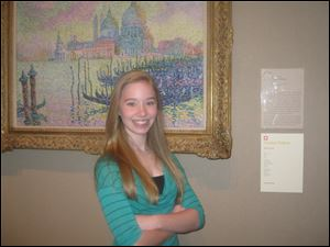 Finalist Hannah Pauley next to her poem on display in the impressionist gallery.