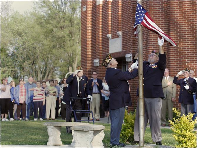 VFW honor guard members Clark Chafin, left, and Scott Goeckerman lower the flag at Walbridge Elementary during a farewell ceremony as alumni, staff, and students look on. The ceremony Tuesday was part of an open house at which the public could learn more about, and tour, the building. It will be closed at the end of this school year.
