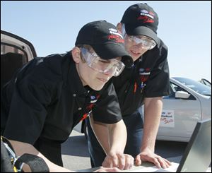 Whitmer High School seniors Josiah Meiring, left, and Mike Stockdale II consult an online serice manual while diagnosing trouble with a new Ford Fusion during the Ford-AAA Auto Skills State Competition.