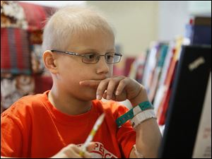 Alex Carman, 8, participates in an online math lesson via Skype, from his room at Toledo Children's Hospital.