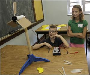 Monroe Zell and Miranda Walker, Harvard Elementary School sixth graders, observe how a change in blade angle affects the speed of their miniature wind turbine. They built it at Monday's summit.