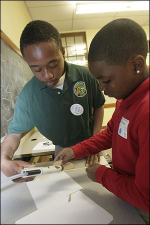Austin Ward, a sophomore at Toledo Technology Academy, holds the glue gun for Richshawn Ticey, a Chase STEM student, as he attaches turbine blades to a skewer.