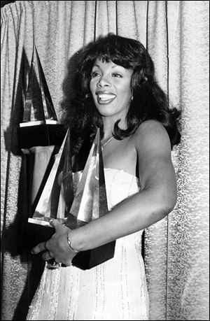 In this Jan. 12, 1979, photo, Donna Summer poses with three awards she won at the American Music Awards in Los Angeles.
