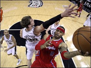 Los Angeles Clippers' Kenyon Martin, right, is defended by San Antonio Spurs' Tiago Splitter, left, as he drives to the basket during the first half of Game 2.