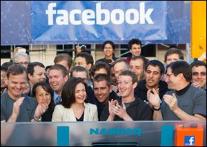 Facebook founder, Chairman and CEO Mark Zuckerberg, center, applauds at the opening bell of the Nasdaq stock market from Facebook headquarters in Menlo Park, Calif.