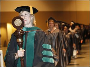 Christine W. Boudrie, M.D., Assistant Professor of Biology & Health Sciences leads the processional as she carries the university's  mace.
