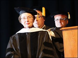 Dr. Elizabeth S. Ruppert, M.D., left, is hooded by Lourdes University president Robert Helmer, PhD., J.D. as she receives an honorary degree. At rear, right, is Joseph T. Nachtrab, chair of the Board of Trustees.