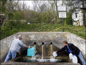 Danny Cantrell, left, and his wife  Rae Jean Cantrell, right, fill water jugs from a spigot called Buchtel Spring in Buchtel, Ohio. The couple and their two daughters do not have running water in their trailer in Glouster, Ohio, about a 10 minute drive from the water.