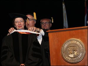 Dr. Elizabeth S. Ruppert, M.D., left, is hooded by Lourdes University president Robert Helmer, PhD., J.D. as she receives an honorary degree.