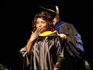 Master ofScience in Nursing graduate Darrah Samuel Obong Okeke blows a kiss to her cheering family as she is hooded by Deborah Vargo, Ph.D.