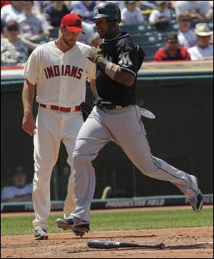The Marlins' Hanley Ramirez, right, crosses the plate to score off teammate Greg Dobbs' double to center in the third inning against the Cleveland Indians. Indians starting pitcher Derek Lowe, left, looks on.
