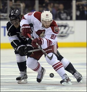 Kings center Anze Kopitar, left,  and Phoenix Coyotes right wing Mikkel Boedker battle for the puck during the first period in Game 4.