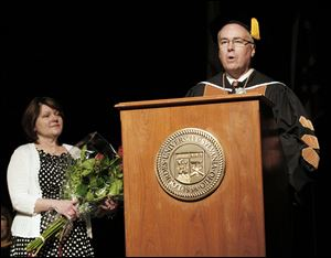 Linda Helmer listens as her husband, outgoing President Robert Helmer, addresses the graduates. He was honored at the ceremony for his service to the university and its values.